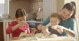 Glückliche Familie, die in der Küche spielt mit dem Teig und den Bestandteilen kocht stock footage