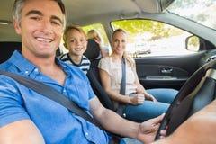 Glückliche Familie, die an der Kamera im Auto lächelt Stockfotografie