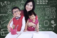 Glückliche Familie, die in der Klasse aufwirft Stockbilder