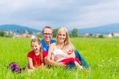Glückliche Familie, die draußen auf Gras sitzt Stockfotografie