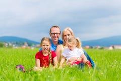 Glückliche Familie, die draußen auf Gras sitzt Stockbilder