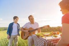 Glückliche Familie, die draußen das Mittagessen genießt Lizenzfreies Stockbild