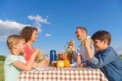 Glückliche Familie, die draußen das Mittagessen genießt Stockbild