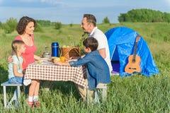 Glückliche Familie, die draußen das Mittagessen genießt Lizenzfreie Stockbilder