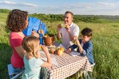 Glückliche Familie, die draußen das Mittagessen genießt Lizenzfreie Stockfotos