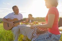 Glückliche Familie, die draußen das Mittagessen genießt Lizenzfreie Stockfotografie
