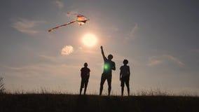 Glückliche Familie, die draußen, Fliegendrachenfliegen spielt Schattenbild von Kindern mit einem Drachen bei Sonnenuntergang Team stock video