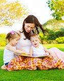Glückliche Familie, die draußen liest Lizenzfreie Stockbilder