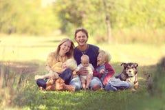 Glückliche Familie, die draußen zusammen mit Hund lacht lizenzfreie stockbilder