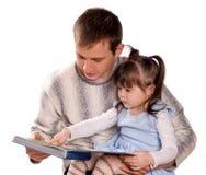 Glückliche Familie, die ein Buch liest Lizenzfreies Stockfoto
