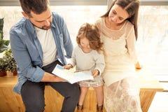 glückliche Familie, die ein Buch zu ihrer Tochter liest Sohn gibt der Mama eine Blume stockfoto