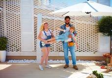 Glückliche Familie, die ein Gitter für Anlagen auf Patio gründet Stockfoto