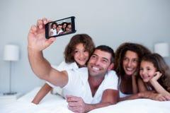 Glückliche Familie, die ein selfie auf Bett nimmt Lizenzfreies Stockfoto