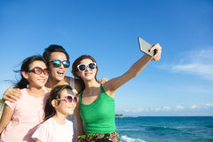 Glückliche Familie, die ein selfie am Strand nimmt lizenzfreie stockfotografie