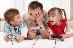 Glückliche Familie, die ein Videospiel spielt Stockbilder