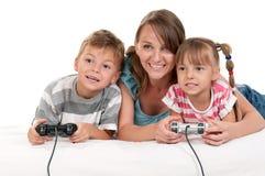 Glückliche Familie, die ein Videospiel spielt Lizenzfreies Stockfoto