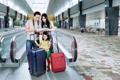 Glückliche Familie, die eine Karte auf Tablette schaut Stockfotografie