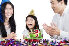 Glückliche Familie, die einen Geburtstag auf Studio feiert lizenzfreie stockbilder