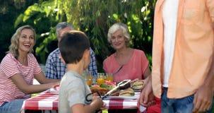 Glückliche Familie, die einen netten Jungen vorbereitet den Grill schaut stock video footage