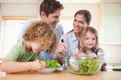 Glückliche Familie, die einen Salat zubereitet Stockbild