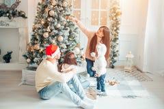 Glückliche Familie, die einen Weihnachtsbaum mit boubles im Wohnzimmer verziert stockfotografie