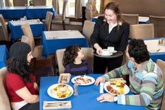Glückliche Familie, die an einer Gaststätte frühstückt Lizenzfreie Stockfotos