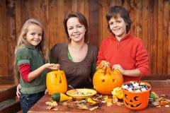 Glückliche Familie, die für Halloween sich vorbereitet Stockbild