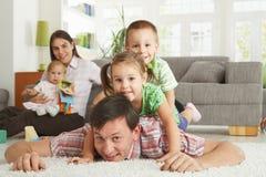 Glückliche Familie, die für Kamera aufwirft Stockfotos
