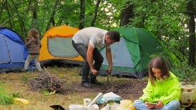 Glückliche Familie, die für Picknick am Campingplatz sich vorbereitet stock video footage