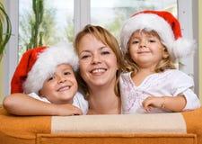 Glückliche Familie, die für Weihnachten sich vorbereitet Stockfotos