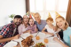 Glückliche Familie, die am festlichen Tisch für Geburtstag aufwirft Stockfoto
