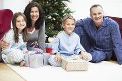Glückliche Familie, die in Front Of Christmas Tree sitzt Stockfotografie