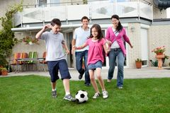 Glückliche Familie, die Fußball in ihrem Hinterhof spielt Stockfoto
