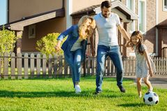 Glückliche Familie, die Fußball im Yard spielt stockbild