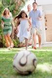 Glückliche Familie, die Fußball spielt und Spaß hat Lizenzfreie Stockfotos