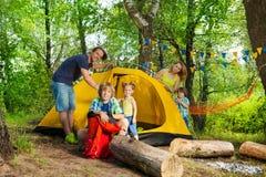 Glückliche Familie, die herauf ein Zelt auf Camping-Ausflug sich setzt lizenzfreie stockbilder