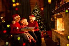 Glückliche Familie, die herein ein Buch durch einen Weihnachtsbaum liest Lizenzfreie Stockbilder