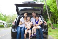 Glückliche Familie, die hinten im Auto und in ihrem Haus sitzt stockfoto
