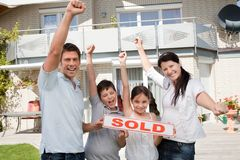 Glückliche Familie, die ihr neues Haus kaufend feiert Stockfotos