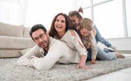 Glückliche Familie, die im bequemen Wohnzimmer sich entspannt lizenzfreie stockfotografie