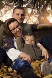 Glückliche Familie, die im Herbstlaub sitzt stockfoto