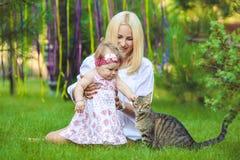 Glückliche Familie, die im Sommergrünpark stillsteht Stockbilder