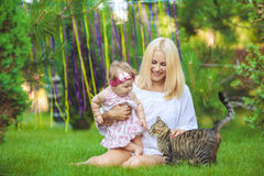 Glückliche Familie, die im Sommergrünpark stillsteht Stockbild