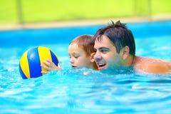 Glückliche Familie, die im Wasserball im Pool spielt Stockfoto