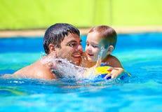 Glückliche Familie, die im Wasserball im Pool spielt Lizenzfreie Stockbilder