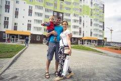 Glückliche Familie, die im Yard eines neuen Hauses steht Lizenzfreie Stockfotografie
