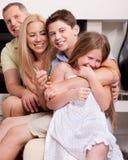 Glückliche Familie, die innen gerade sitzt und Spaß hat lizenzfreie stockbilder