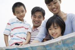 Glückliche Familie, die Karte gegen Himmel betrachtet Stockfotografie
