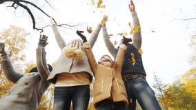 Glückliche Familie, die mit Herbstlaub im Park spielt stock footage