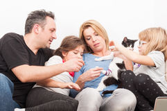 Glückliche Familie, die mit Katze oder Haustier spielt Stockbilder